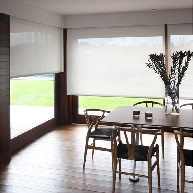 Matsalsmöbel och rullgardiner framför stora fönster.